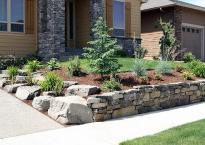 Hand Stacked Natural Rock Wall and Residential Landscape