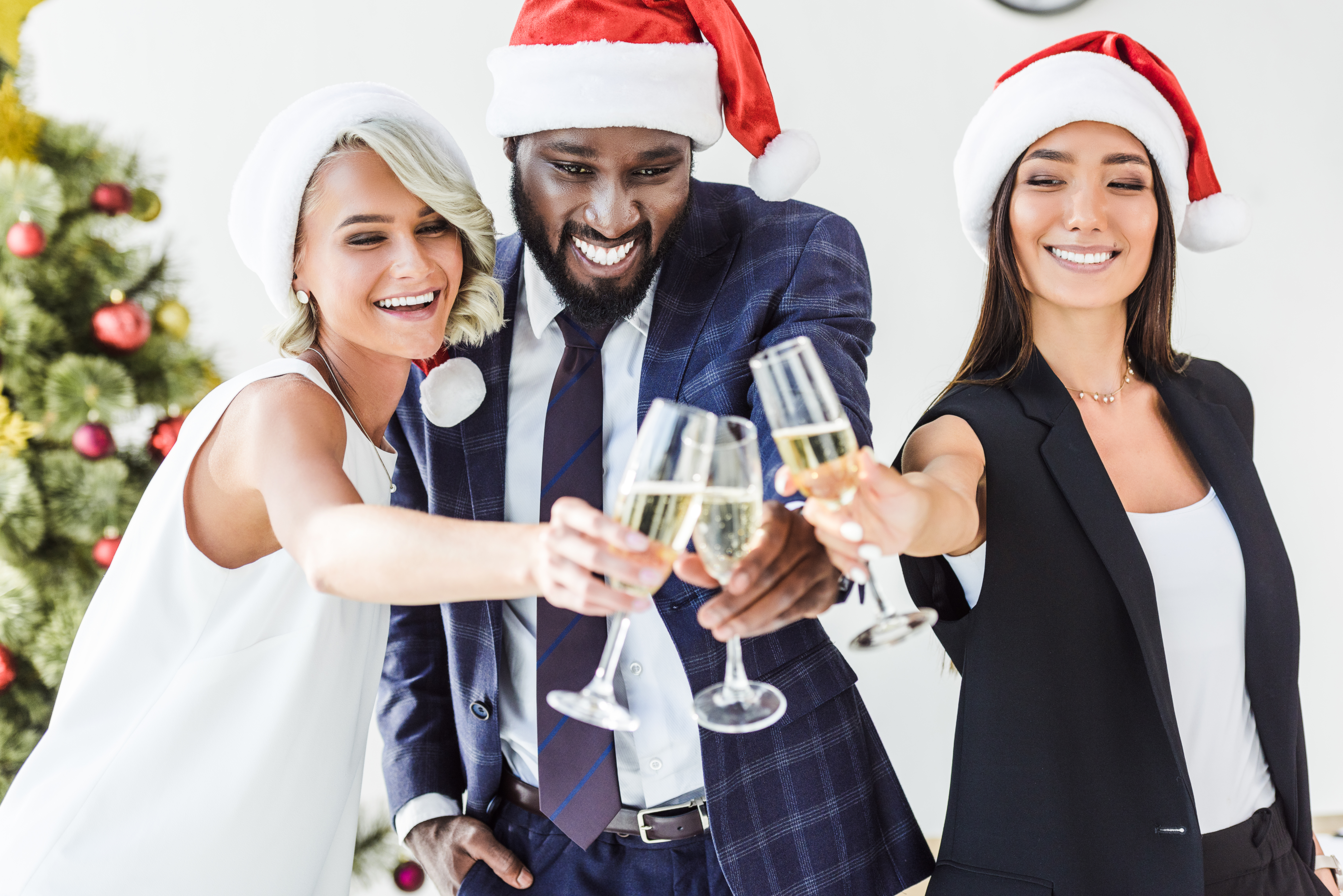 Three adults wearing Santa hats clink champagne glasses together during a holiday party.